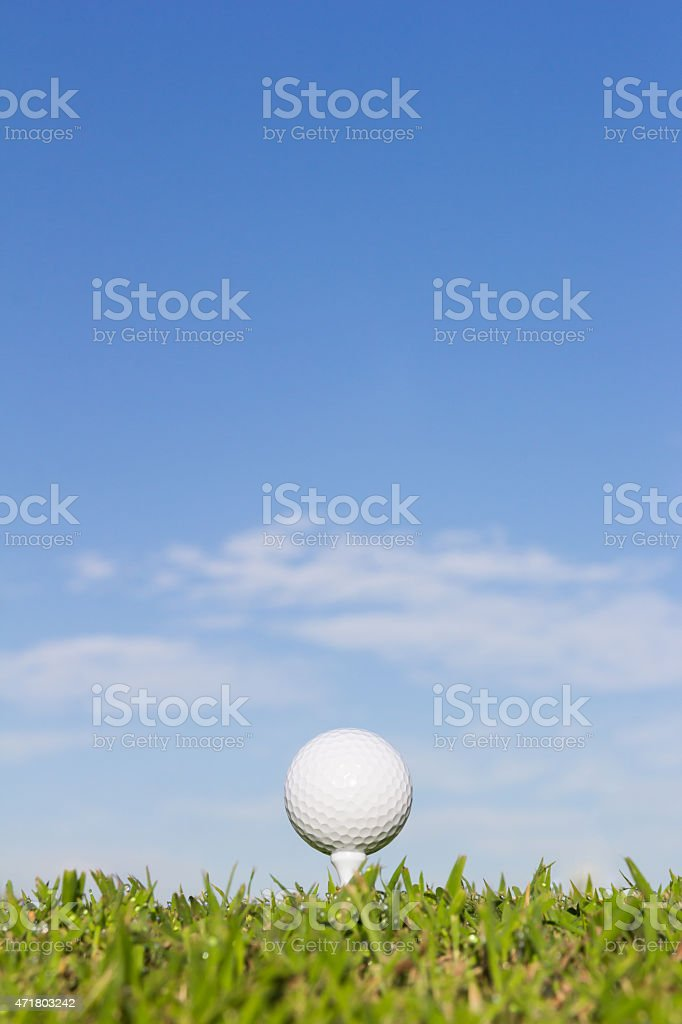 Golf ball on a tee with cloud and sky background