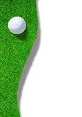 Golf ball at the edge of sand trap bunker on white background with copy space. Vertical orientation.