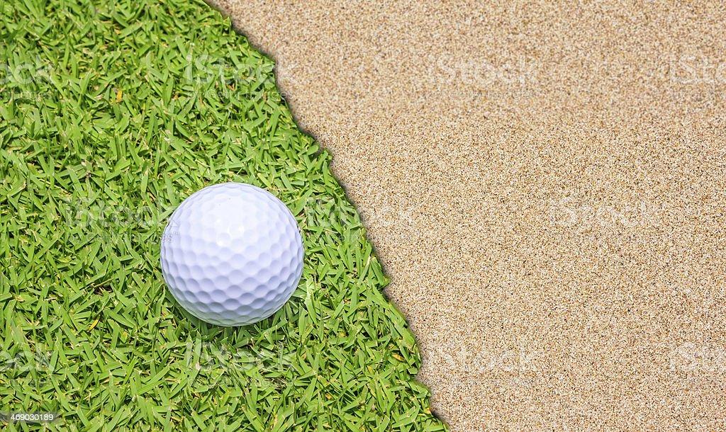 Golf ball on grass near sand bunker
