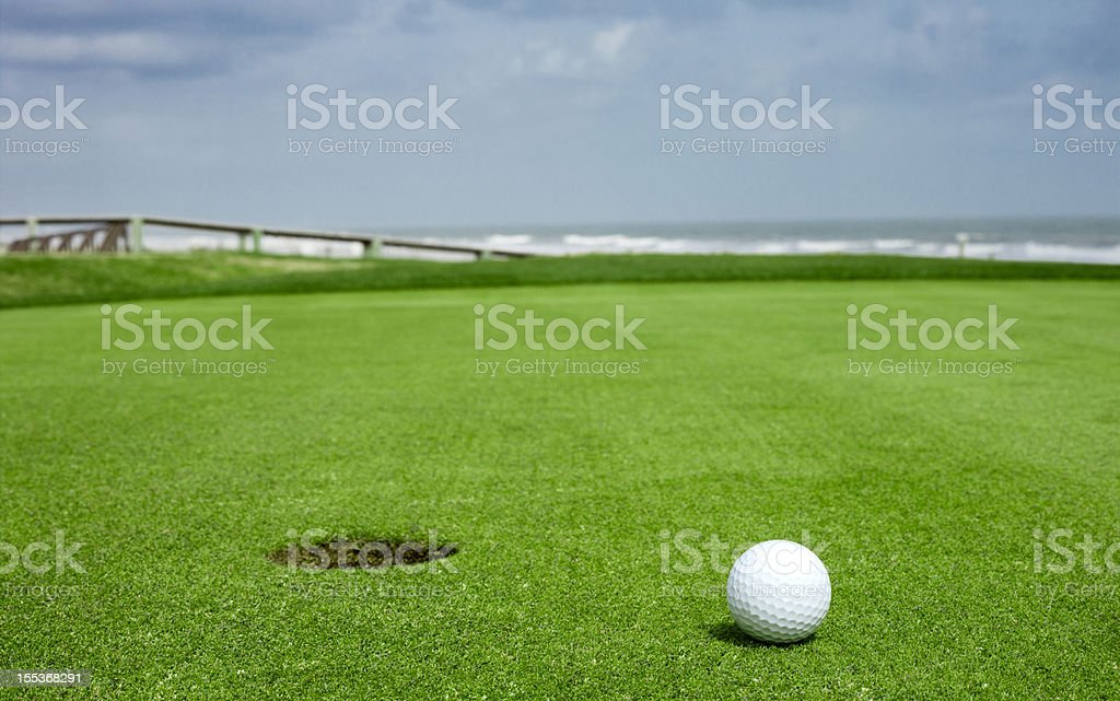 Golf ball on green close to the hole stock photo