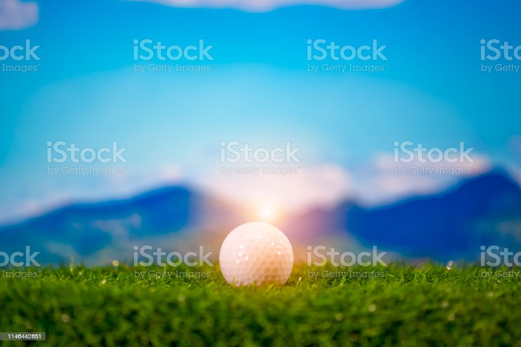 Golf ball on green golf course on hills and blue sky sunset
