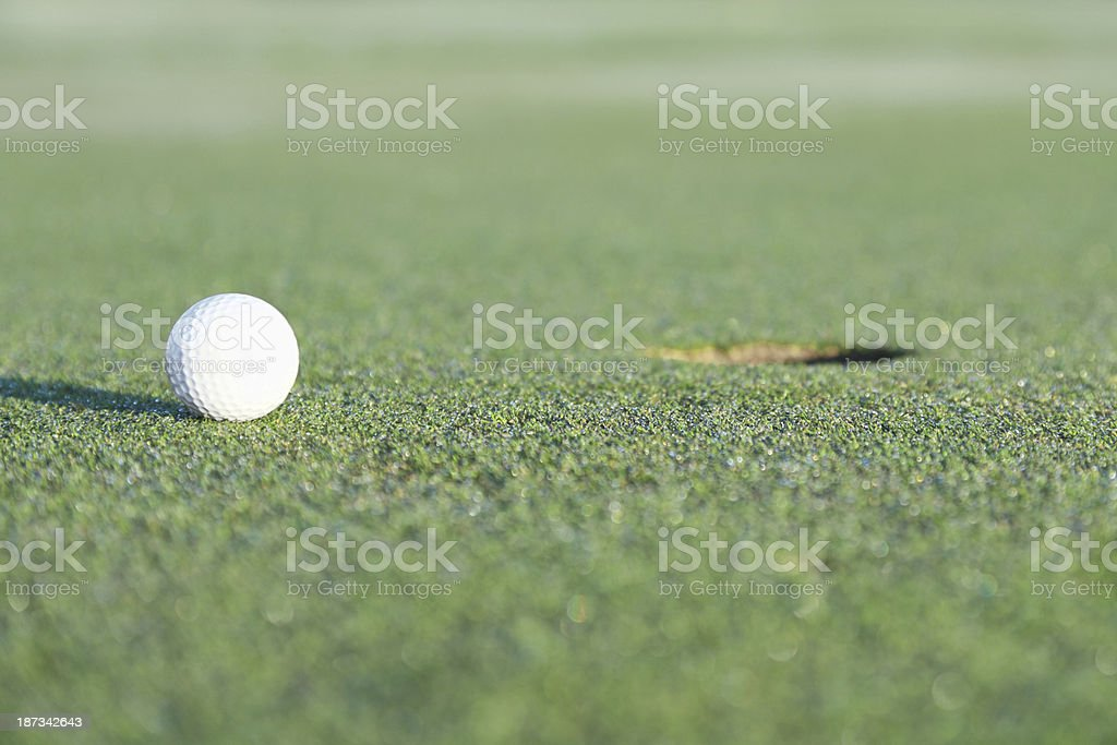 Golf ball on green grass by the hole