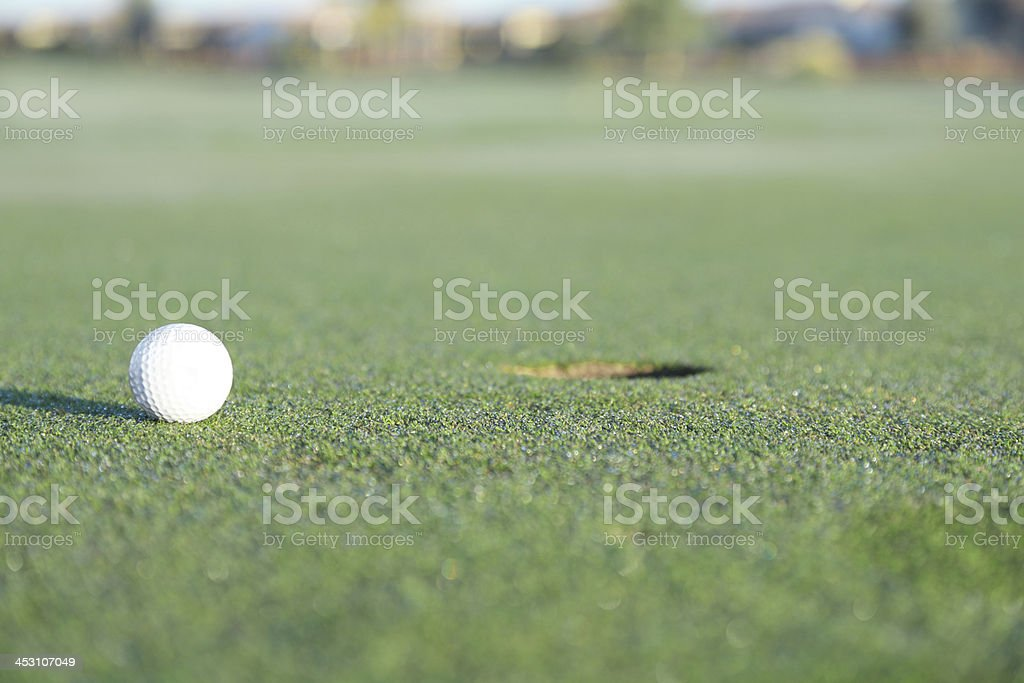 Golf ball on green grass by the hole stock photo