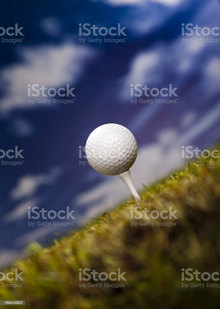 Golf ball on green grass over a blue sky royalty-free stock photo