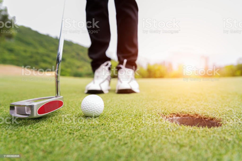 Golf ball on green grass ready to be struck at golf club,close up in...