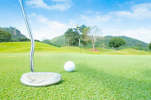 istock golf ball on green grass ready to putt on green in beautifull tropical golf course for background or poster. 1055107490