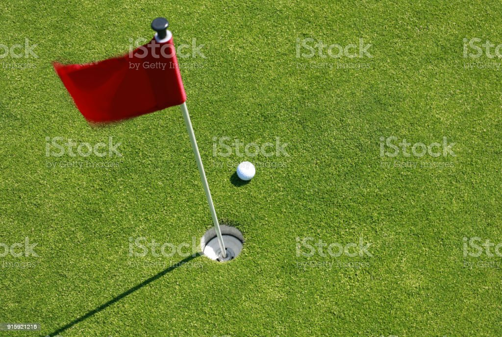 Golf ball on green with flag. stock photo