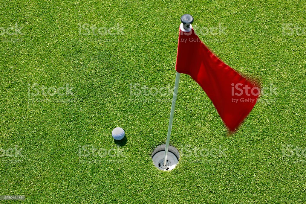 Golf ball on green with red flag. stock photo