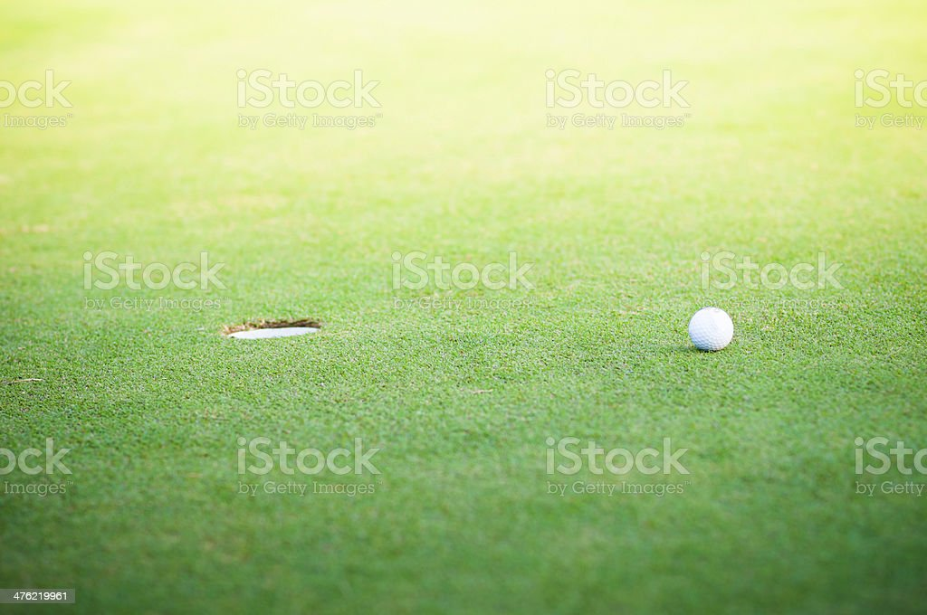 Golf ball on lip of cup royalty-free stock photo