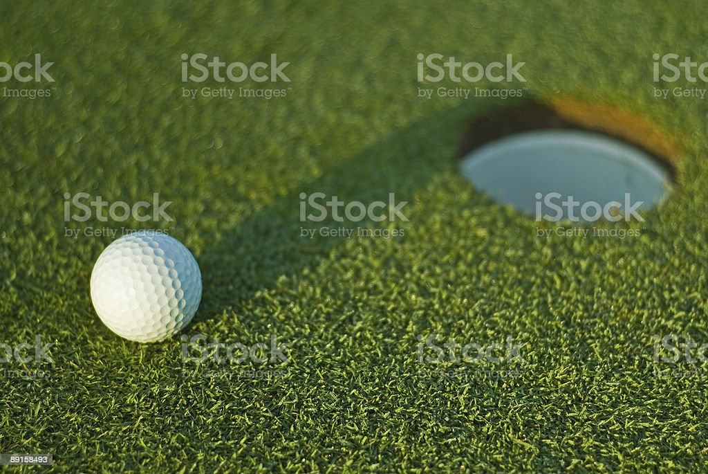 Golf ball on next to hole 1 royalty-free stock photo