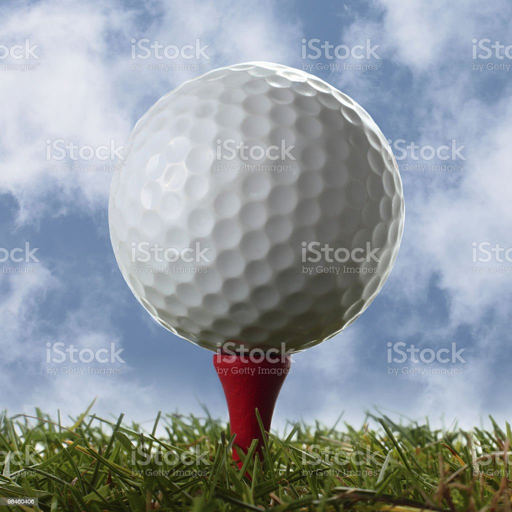 Golf ball on red tee above real grass royalty-free stock photo