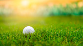 Closeup shot of a golf ball on top of a golf peg with a golf club next to it about to hit it outside during the day