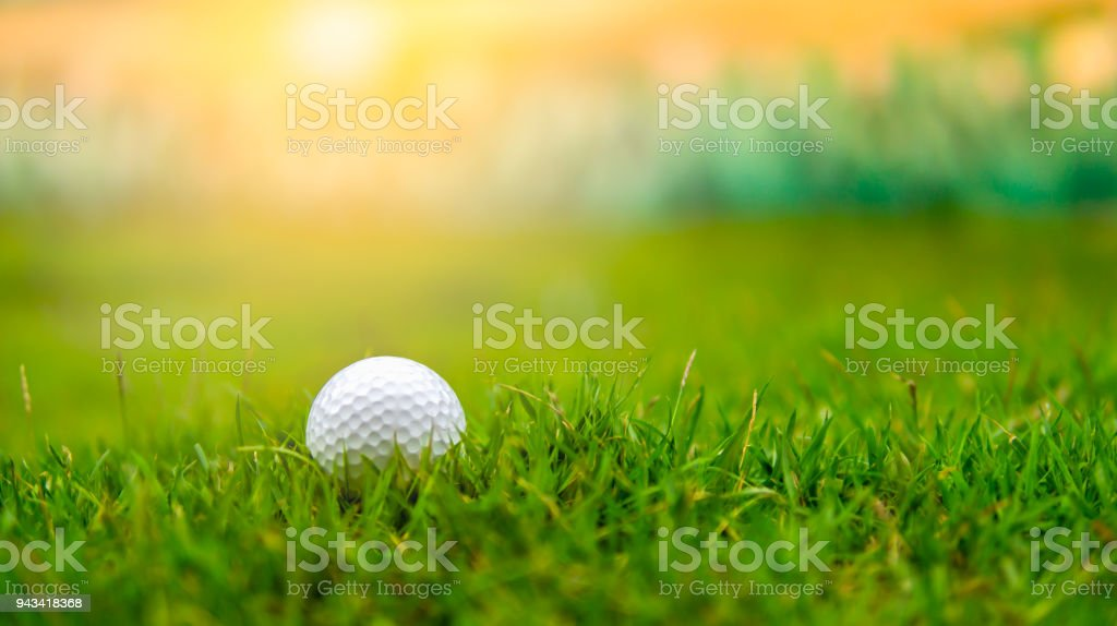 Pelota de golf en la calle de hierba áspera en puesta de sol - foto de stock
