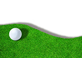 Golf ball on edge of sand trap bunker on white background with copy space.