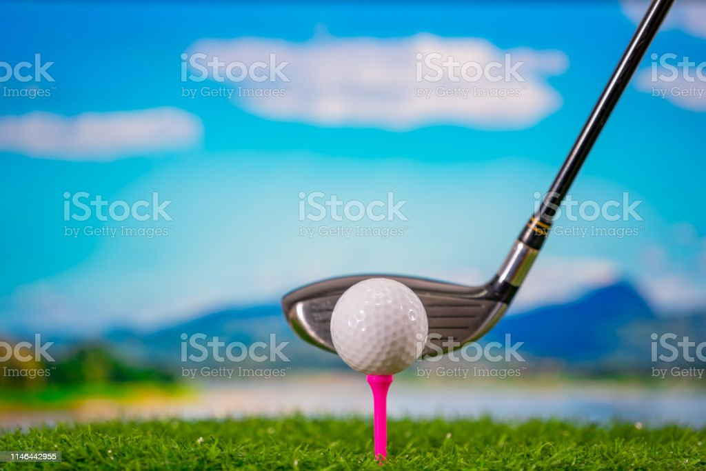 Golf ball on tee and golf club hitting ball on hills and blue sky...