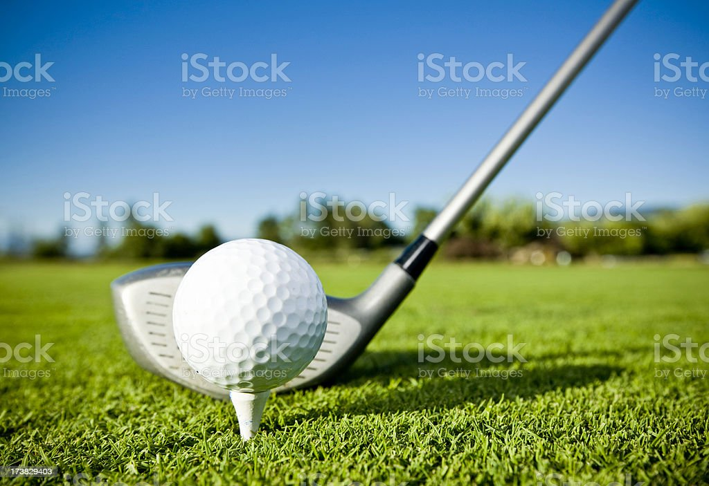 Golf ball on tee and golf club on golf course stock photo