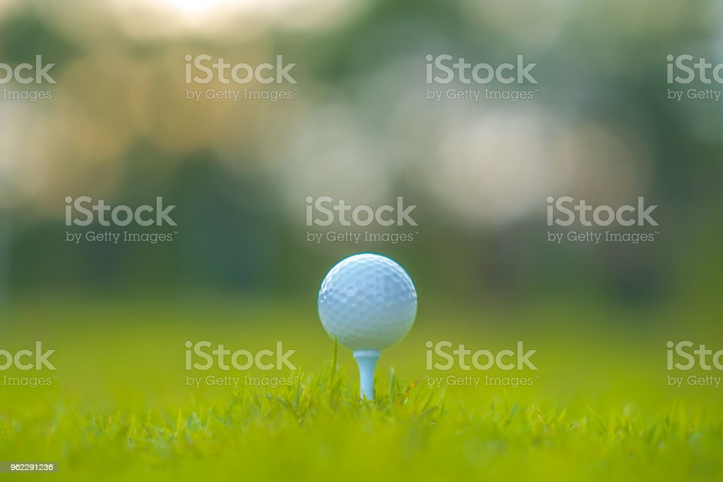 Golf ball on tee for golfer hitting to hole in beautiful fairway and...