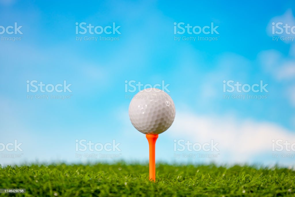 Golf ball on tee in tee off zone on grass and blue sky and cloud...