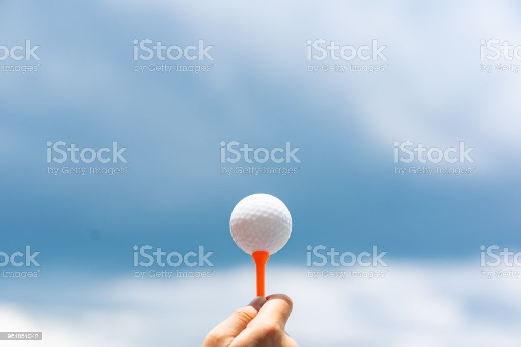 Golf ball on tee on sky blue and cloud background royalty-free stock photo