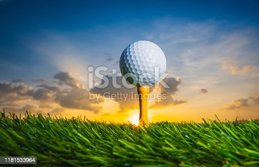 golf ball on tee pegs ready to play in the golf course at sunset with clouds in the evening day background, sport outdoor