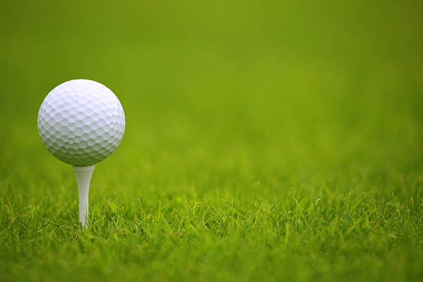 Golf ball on tee White Golf ball on tee on green grass of golf course golf ball stock pictures, royalty-free photos & images