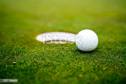 Golf ball on the green next to the hole