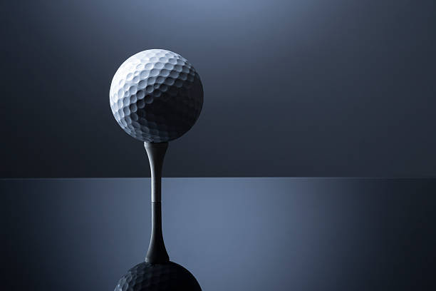 Golf ball over tee isolated on dark blue reflective background. stock photo
