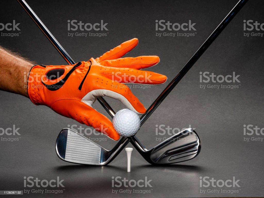 Man\'s hand holding a golf ball