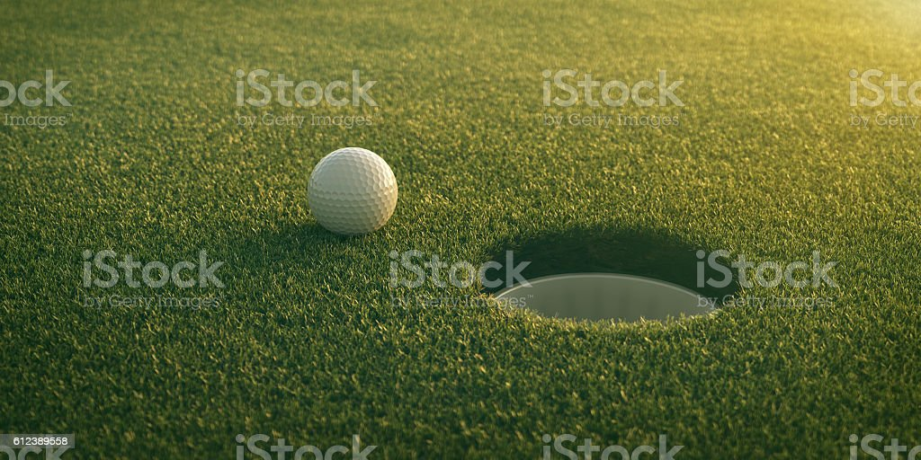 Golf ball rolling towards hole stock photo