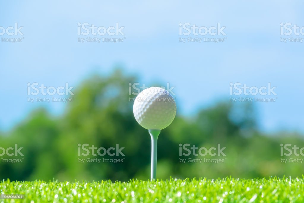 Golf ball sitting on tee on sky blue or azure sky and cloud background
