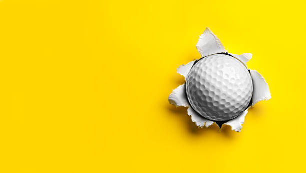 Golf Ball stuck in Yellow Paper Golf Ball stuck in yellow paper.  burwellphotography stock pictures, royalty-free photos & images