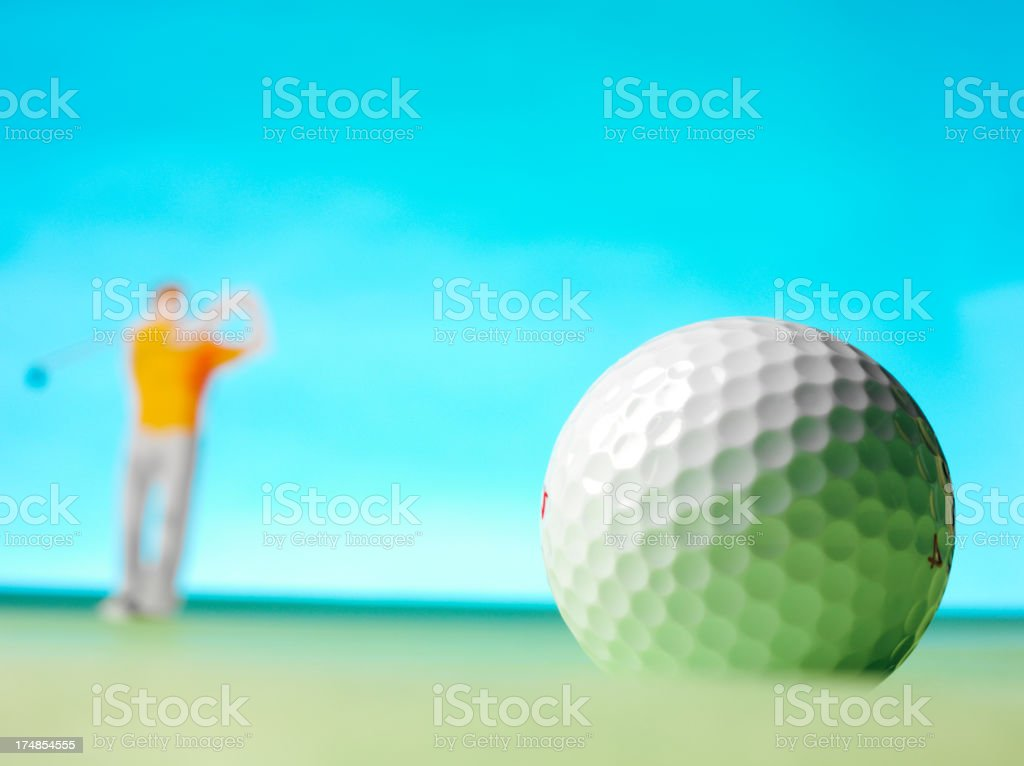 Golf Ball with a Golfer and Blue Background royalty-free stock photo