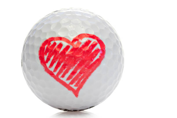 Golf ball with a red heart stock photo