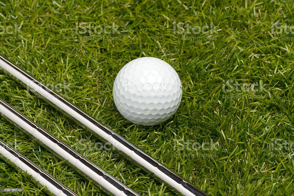Golf irons steel shaft on a green grass arranged diagonally with a...