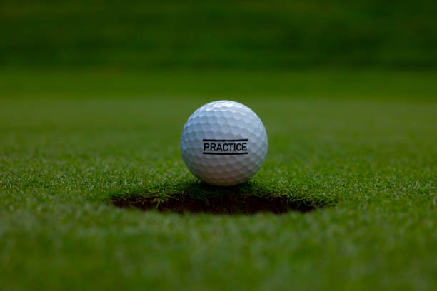 Golf Ball with Letter PRACTICE Leaning on the Golf Hole stock photo