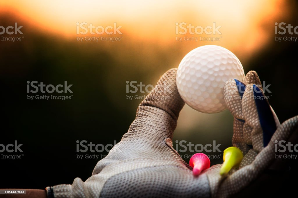 Golf balls and tee in the hands that are worn with white gloves.In...