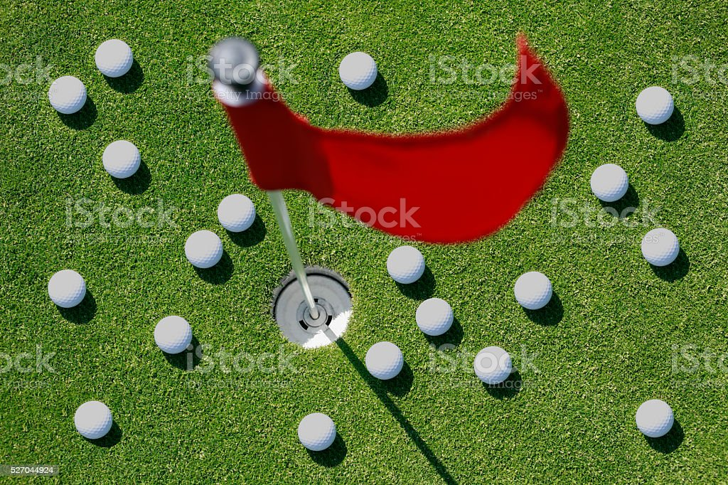 Golf balls on green with red flag. stock photo