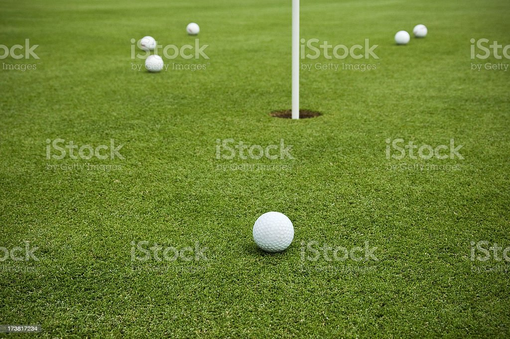 A group of golf balls on the putting green around the hole. Shallow...