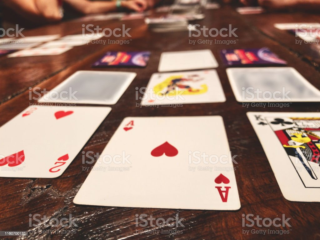Playing Golf Card Game on Rustic Wood Dining Table Card playing...