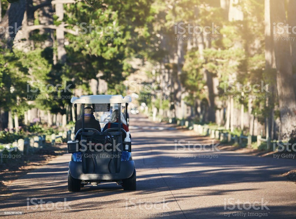 Golf cart driving down beautiful leafy avenue stock photo