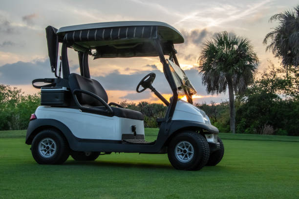 Golf cart on course Golf cart on Florida golf course at sunset golf cart stock pictures, royalty-free photos & images