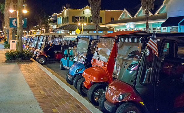Golf Carts in a Row Golf Carts Parked in a Row in The Villages, Florida. golf cart stock pictures, royalty-free photos & images