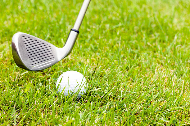 Golf club and ball on ruff grass stock photo