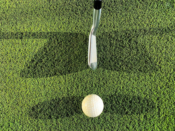 Golf Club and Ball with Double Shadow on Mat on Driving Range stock photo