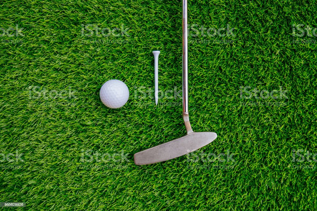 Golf club and golf ball and tee on green grass