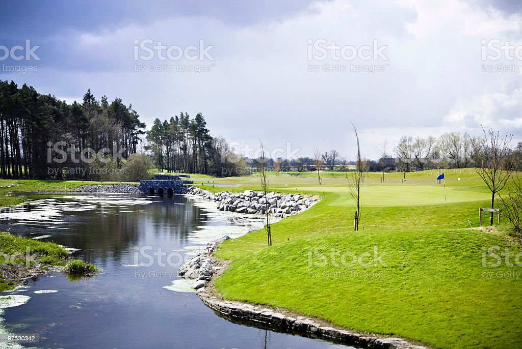 Golf Club green with water hazard in foreground royalty-free stock photo