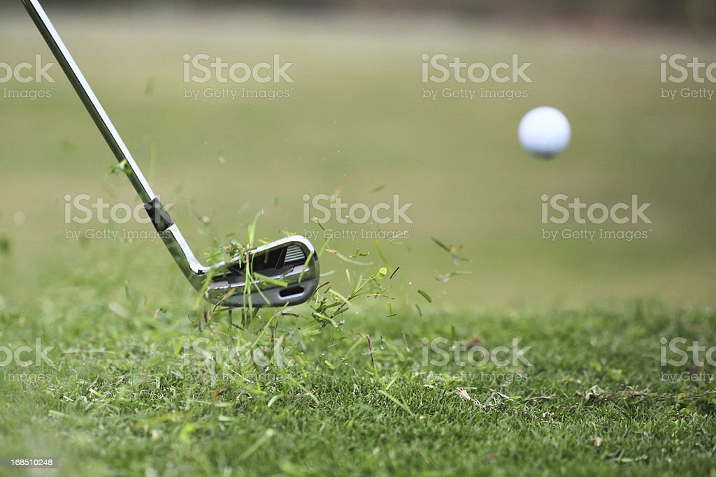 Golf Club Hits Ball in the Air with Grass Flying stock photo