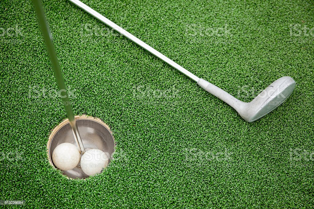 Putting golf club on green grass with golf ball in the hole - top view