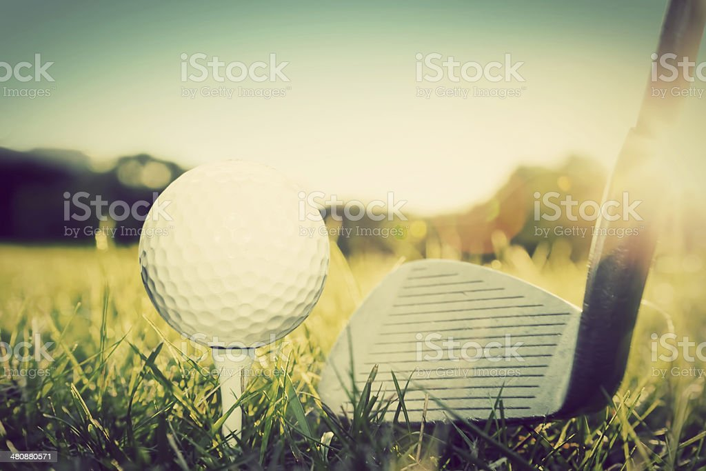 Golf club ready to hit ball at golf course stock photo