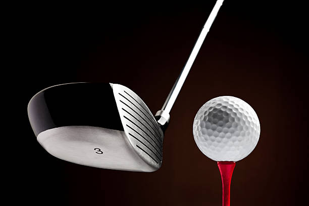 golf clubhead hitting a ball on the tee - golf clubs stock photos and pictures